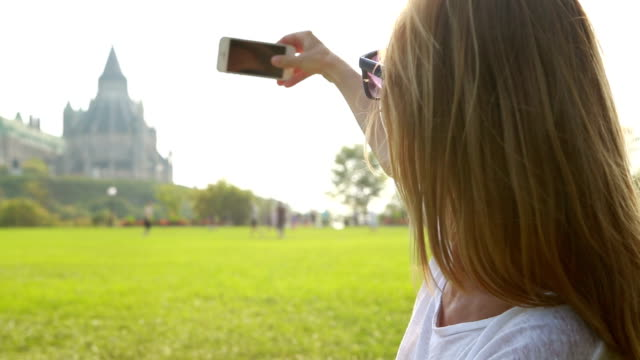 Beautiful young woman taking picture in Ottawa using mobile phone