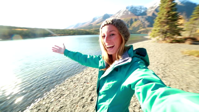 Beautiful young woman taking selfie portrait by the  lake in Canada
