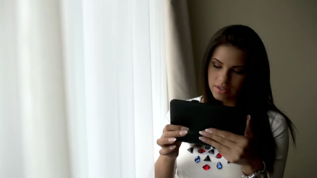 Beautiful Young woman uses a digital tablet near window