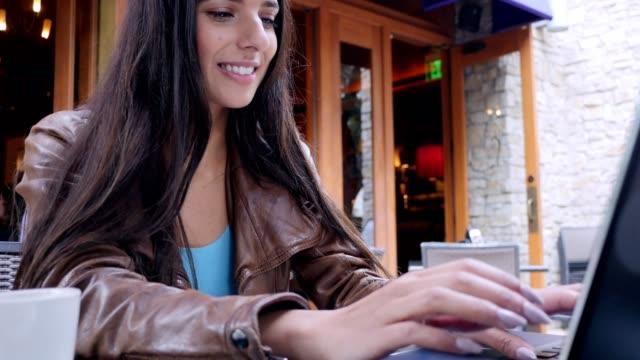 Schöne junge Frau nutzt Laptop im Café im freien