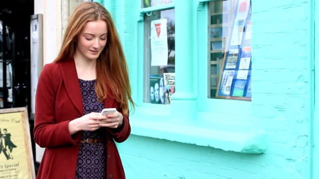 Schöne junge Frau, die Ihr smartphone zu Fuß.