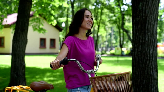 Beautiful young  woman with old vintage bike in city park area