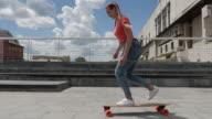 Beautiful youth riding skateboard outdoors