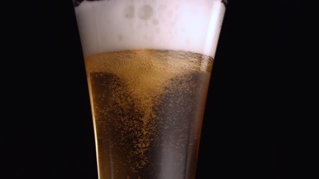 CU SLO MO Beer swirling in pilsner glass / Studio, New Jersey, USA