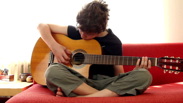 Anfänger Junge spielt Gitarre wie zu Hause fühlen.