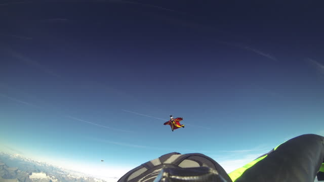 POV behind a wingsuit skydivers as other wingsuit skydivers approach and fly in formation