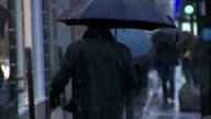 WS Behind man in overcoat walking up city sidewalk in rain w/ umbrella raindrops dripping off exhaled breath visible once green traffic light...