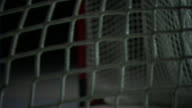 Black ice hockey puck flying into goal hitting white net net rebounding amp coming to rest dark BG Slap shot sports score scoring shot on goal SOG...