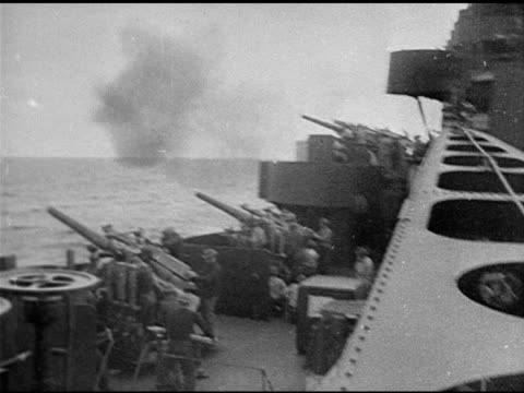 Behind Sailor in rain gear watching ship in rough seas VS Gun Crews firing antiaircraft guns artillery Explosions in water WWII World War II