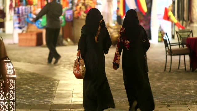 Behind two unidentifiable women dressed in traditional clothing walking through market unidentified men in modern traditional clothes storefront BG