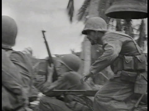 Behind US Marine firing rifle PAN Marines behind cover on beachfront World War II WWII