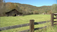 WS Old wooden weathered pitched roof barn in grass pasture tree covered mountain BG Americana farm farming vintage rural Lifestyle