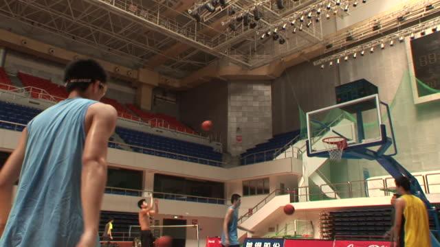 MS, Beijing Jinyu Ducks basketball players shooting hoops in stadium, Beijing, China