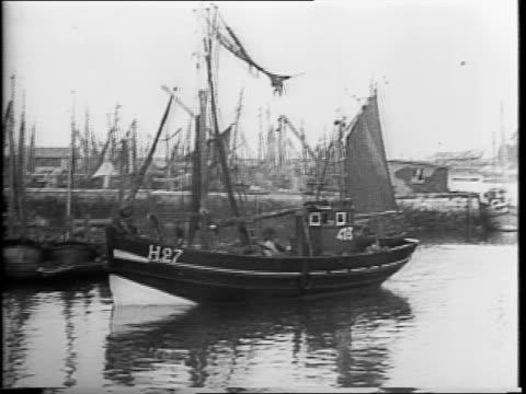Belgian fisherman sitting on Dock / closeup view of fishing boats / fishing boats at sea / montage of women working on fishing nets / fishermen...