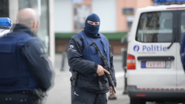 Belgian police secure the area where shots were fired during a counterterrorism raid on a house in Brussels Belgium on March 15 2016 Four police...