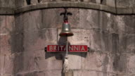 A bell hangs above a sign with the name 'Britannia' on it. Available in HD.