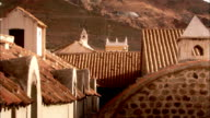 Bell towers and steeples among the rooftops of a village at the foot of a hill in Bolivia. Available in HD.