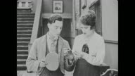 Buster Keaton's hands are inspected by Miss Cutie Cuticle (Alice Lake) who looks at them disapprovingly, so he scrubs them with mop water when she leaves the room