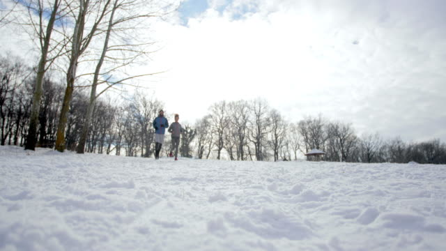 Below view of athletic people running on a snow in winter park.