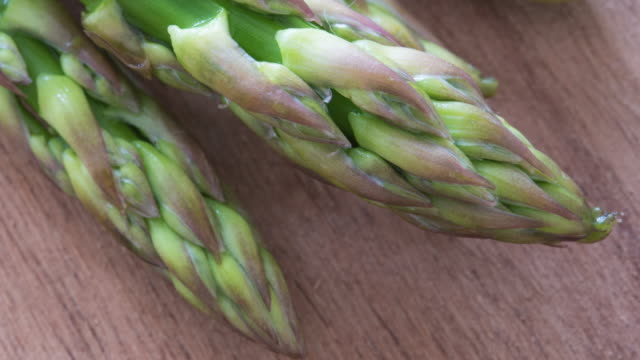 Benefits of Asparagus: close up macro of the popular healthy vegetable over a cooking board in kitchen