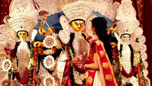 Bengali woman applying tika on goddess durga forehead, Delhi, India