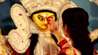 Bengali woman applying tika on goddess durga forehead, Delhi, India