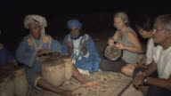 MS PAN Berbers and guests playing traditional music at campsite at edge of desert, Merzouga, Morocco