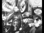 Berlin Nazi party official Joseph Goebbels speaks emphatically at propaganda march of SA stormtroopers in 1929 Berlin with swastikas on flags behind...