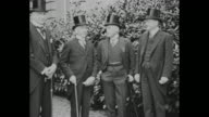 Bernard Baruch Norman Davis Vance McCormick and Herbert Hoover stand outdoors in suits and top hats during June 1919 peace conference in Brussels /...