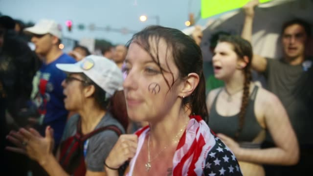 Bernie Sanders supporters one with a peace sign painted on her face shout 'Black Lives Matter' during a torrential downpour outside the Wells Fargo...