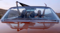 Best friends in shiny red convertible throw hands in air and cheer on Vegas road trip.