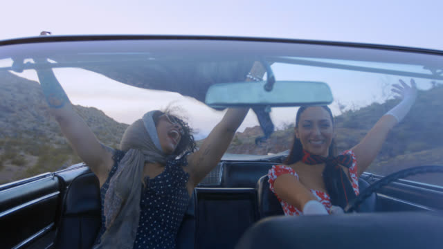 Best friends on Vegas road trip in classic convertible throw hands in air and cheer.