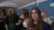 Between Zosia Mamet talking to reporter w/ Allison Williams in BG and HBO logo/ Girls backdrop on the red carpet at the School of Visual Art