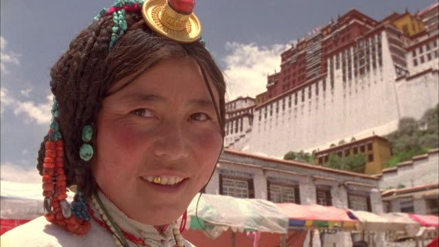 Bhutanese woman with one gold tooth smiles at camera wearing traditional costume, with mountain palace in background Available in HD.