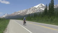 WS Bicycle rider and traffic moving on road through Icefields Parkway near Bow Lake / Banff Nationalpark, Alberta, Canada