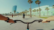 POV bicycle riding in Barceloneta beach during summer vacations