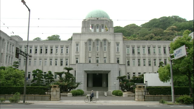 A bicyclist passes in front of the  Ehime Prefectural Government Office in Matsuyama, Japan.