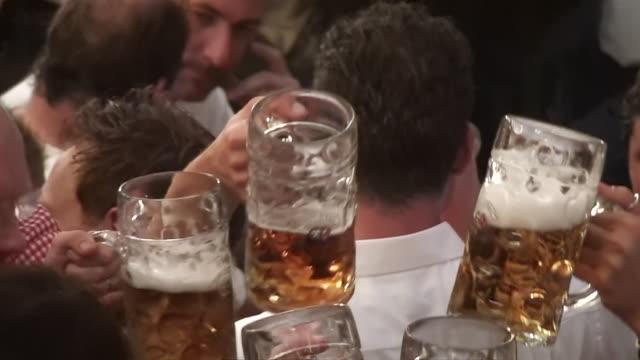 CU big beer glasses bumping together on Oktoberfest / Munich, Bavaria, Germany
