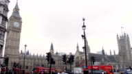 Big Ben and red London bus turning in slow motion