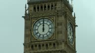Bells go silent for four years ENGLAND London Westminster EXT Big Ben clock face striking 12 and bong sounding PULL OUT people in Parliament Square...