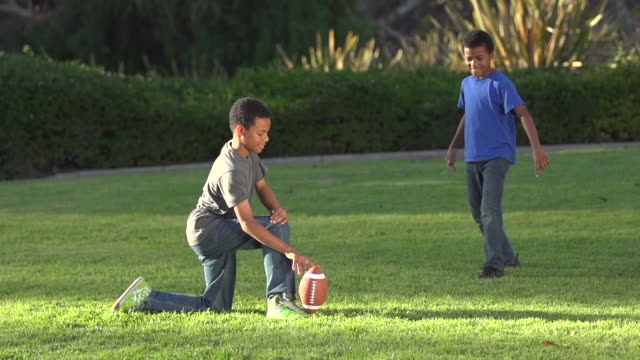 Big brother playing a trick on little brother as he tries to kick a football.
