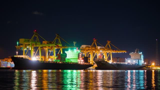 Großer Kran bridge shipping container cargo in der Werft in der Nacht. Logistik Import Export Hintergrund