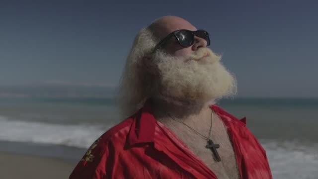 M/S big man w/ white long hair (Santa Claus), beard and moustache, sunglasses and hawaiian shirt in the beach