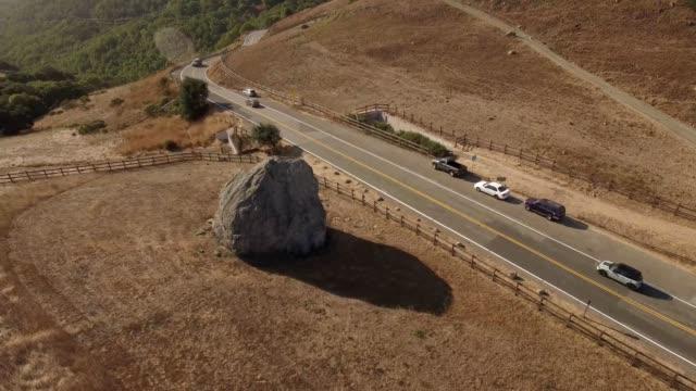 Big rock next to valley road at sunrise, circling shot