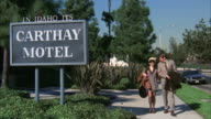 MS PAN Big sign board of in idaho its carthy motel and couple walking from near hotel
