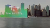Big transparent Welcome to New York City sign dragging after boat