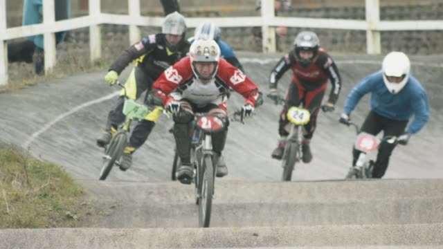 BMX bike riders racing towards the camera on an outdoor dirt track Patchway BMX Winter Series Bristol UK NO