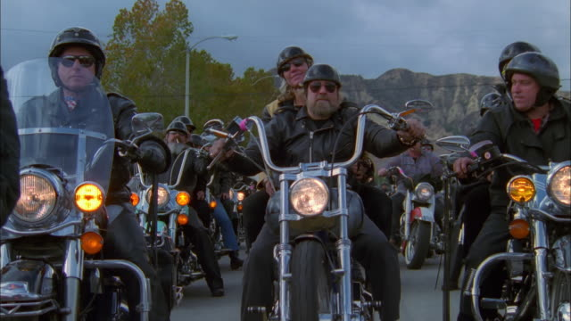 Biker couple ride towards camera past gang of fellow bikers, California Available in HD.