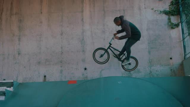 BMX biker jumping in half pipe