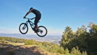 SLO MO MTB biker jumping on a downhill trail